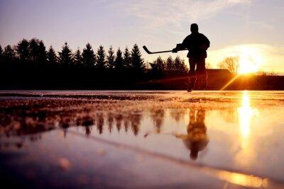 Reflexion der jungen Hockeyspieler auf hellem Natur-Eis während bunten ruhigen Wintersonnenuntergang am Januar gefrorenen See