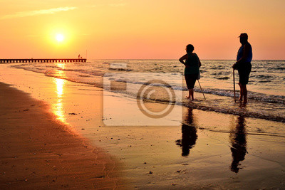 Retired people walking on the beautiful morning beach during sunrise
