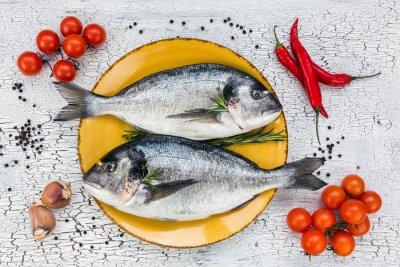 Sticker Rohe frische Dorade Fisch auf gelbem Teller und Gemüse auf weißem Tisch. Draufsicht.