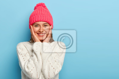 Sticker Romantic positive young European woman smiles gently, has white perfect teeth, touches both cheeks, has friendly look, wears pink hat with pompon and white sweater, models against blue wall.