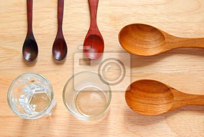 Sammlung von hölzernen Kochlöffel mit kleinen Gläsern auf Holz