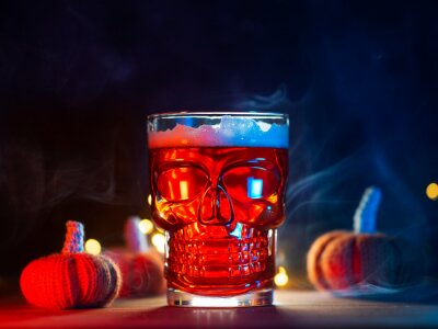 Sticker Scary glass of beer in the shape of a skull, Halloween party. Craft beer, pumpkin ale
