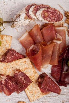 Sticker Schinken, Nüsse, Cracker und Trauben auf weißem hölzernem Hintergrund