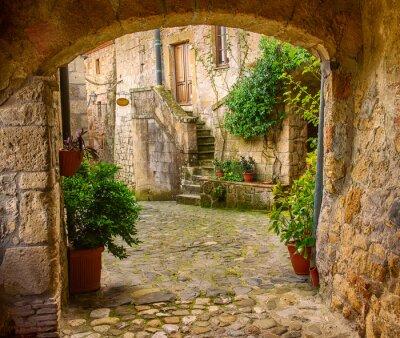 Sticker Schmale Straße der mittelalterlichen Tuff-Stadt Sorano mit Bogen, grüne Pflanzen und Kopfsteinpflaster, Reise Italien Hintergrund