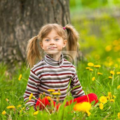 Sticker Schöne Fünf-Jahres-Mädchen sitzen im Gras
