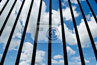 schwarzen Eisenzaun mit bewölkten blauen Himmel Hintergrund