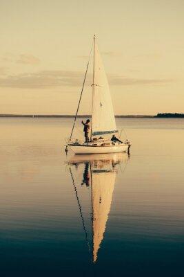 Sticker Segelboot auf einem ruhigen See mit Reflexion im Wasser. Ruhige Szene Landschaft.