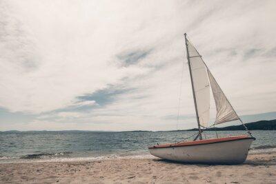 Sticker Segelboot auf tropischen Strand mit blauem Wasser Hintergrund