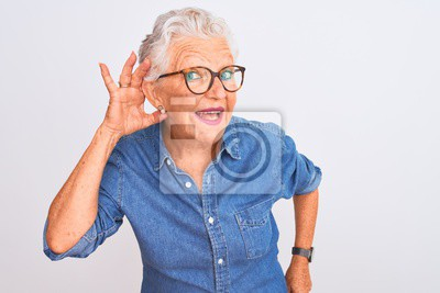 Sticker Senior grey-haired woman wearing denim shirt and glasses over isolated white background smiling with hand over ear listening an hearing to rumor or gossip. Deafness concept.