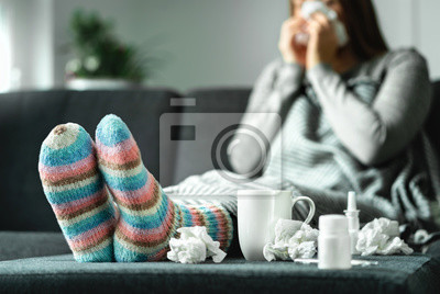 Sticker Sick woman with flu, cold, fever and cough sitting on couch at home. Ill person blowing nose and sneezing with tissue and handkerchief. Woolen socks and medicine. Infection in winter. Resting on sofa.