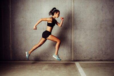 Sticker Slim attraktive Sportlerin läuft gegen eine Betonmauer