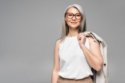 Sticker smiling asian businesswoman in eyeglasses isolated on grey
