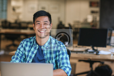 Sticker Smiling young Asian designer using a laptop at his desk