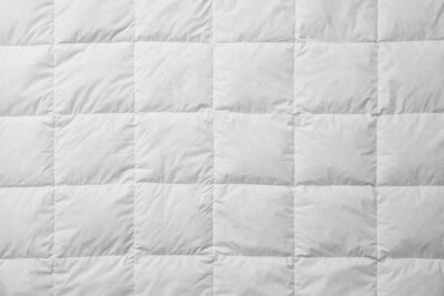 Sticker Soft quilted blanket as background, top view