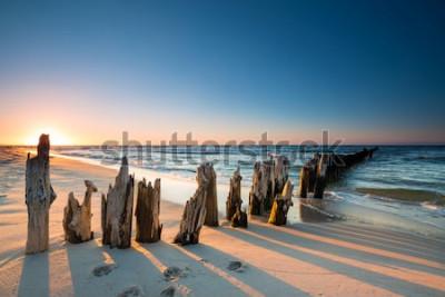 Sticker Sonnenuntergang am Ostseestrand und alten hölzernen Wellenbrecher