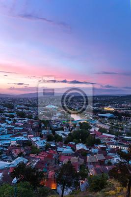 Sonnenuntergang Blick auf Tbilissi, Hauptstadt von Georgien Land, aus Narikala Festung. Berühmte Wahrzeichen - Präsidentenverwaltung, Friedensbrücke mit Beleuchtung.