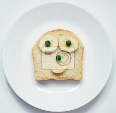 Stock-Foto-schön-Essen-für-Frühstück-für-Kinder-in-der-Form-von-einem-offenen-Sandwich-von-Weiß-frisch-Brot-gelb-Banane-und-Erbsen- auf dem Teller-und-auf-dem-weißen-Hintergrund
