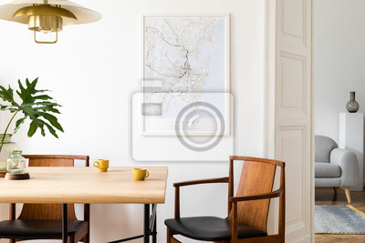 Sticker Stylish and eclectic dining room interior with mock up poster map, sharing table design chairs, gold pedant lamp and elegant sofa in second space. White walls, wooden parquet. Tropical leafs in vase.