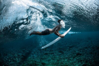 Sticker Surfer performs dive (the duck dive) with his surfboard under the wave and exhales air into the water.
