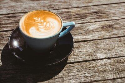 Sticker Tasse Cappuccino mit Kaffee-Kunst auf Holztisch