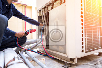 Sticker Technician is checking air conditioner ,measuring equipment for filling air conditioners.