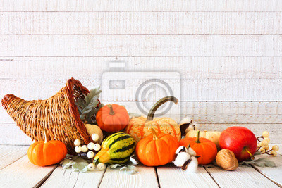 Sticker Thanksgiving cornucopia filled with autumn vegetables and pumpkins against a rustic white wood background
