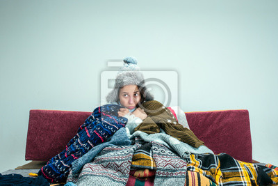 Sticker The young sick woman with flue sitting on sofa at home or studio covered with knitted warm clothes. Illness, influenza, pain concept. Relaxation at Home. Healthcare Concepts.