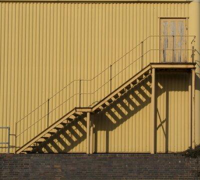 Sticker Treppen führen über eine Metall sidinf Wand.