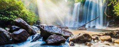 Sticker Tropischer Wasserfall im Dschungel mit Sonnenstrahlen
