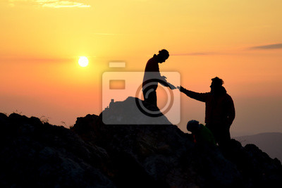 Two friends helping each other and with teamwork trying to reach the top of the mountains during wonderful summer sunrise.