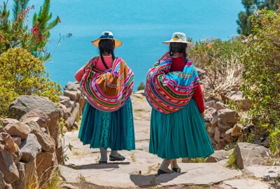Sticker Two indigenous Quechua women in traditional clothes walking down the path to the harbor of Isla Taquile (Taquile Island) with the Titicaca Lake in the background, Peru.