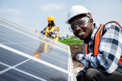Sticker Two workers technicians installing heavy solar photo voltaic panels to high steel platform in corn field. Photovoltaic module idea for clean energy. Green energy concept