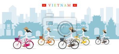 Vietnamesische Frauen mit konischen Hut Reiten Fahrräder, Wahrzeichen Hintergrund
