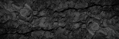 Sticker Volumetric rock texture with cracks. Black stone background with copy space for design. Wide banner.