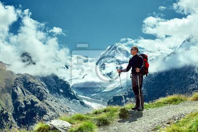 Wanderer an der Spitze eines Passes mit Rucksack genießen sonnigen Tag in den Alpen. Schweiz, Trek bei Matterhorn.