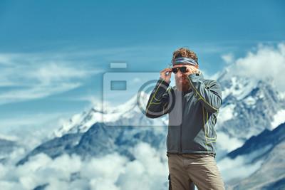 Wanderer an der Spitze eines Passes Setzt auf Sonnenbrillen und genießt sonnigen Tag in den Alpen. Schweiz, Trek bei Matterhorn.