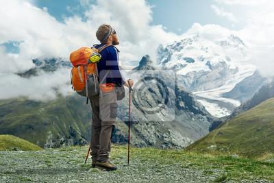 Wanderer mit Rucksack steht auf dem Weg in den Apls Bergen. Trek in der Nähe von Matterhorn Mount. Bergkamm und blauer Himmel auf dem Hintergrund