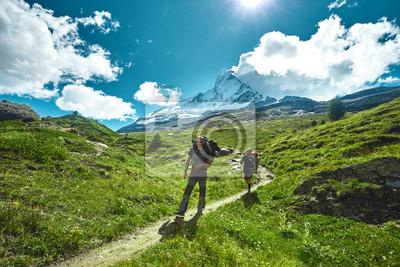 Wanderer mit Rucksäcken auf dem Weg in den Apls Bergen. Trek in der Nähe von Matterhorn Mount