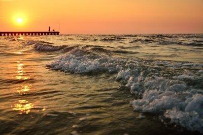Wave auf dem ruhigen Meer in Italien in der Nähe von Strand mit alten Fischer während wunderbaren und bunten Sommer Sonnenuntergang