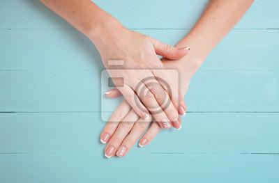 Weibliche Hände mit schöner Maniküre auf einem Hintergrund von blauen Brettern. Nahansicht