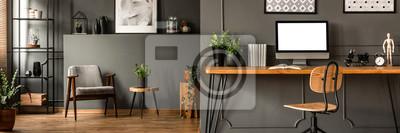 Sticker Wohnzimmerinnenraum des dunklen offenen Raumes mit Metallzahnstange, grauer Lehnsessel und Anlagen im Hintergrund- und Studienecke Haarnadelschreibtisch, Bücher und leerer Monitor im Vordergrund