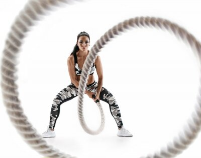 Sticker Woman doing exercises with battle rope. Photo of muscular model in military sportswear isolated on white background. Strength and motivation