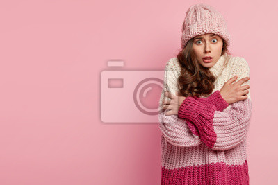 Sticker Worried European woman trembles with fright, crosses hands over chest, doesnt likes freezing chilling weather, wears warm hat and knitted oversized jumper, stands over pink wall with empty space