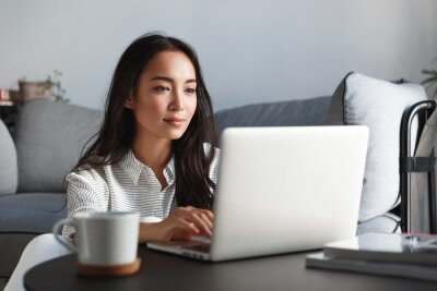 Sticker Young ambitious asian girl working remote from home, looking at laptop screen and smiling. Woman checking mail or researching while telecommuting, sitting on floor at her apartment