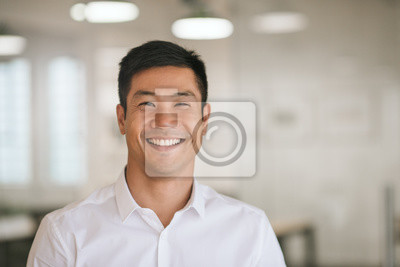 Sticker Young Asian businessman standing in an office smiling confidently