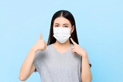 Sticker Young Asian woman wearing face mask to protect from COVID-19 and giving thumbs up isolated on light blue background