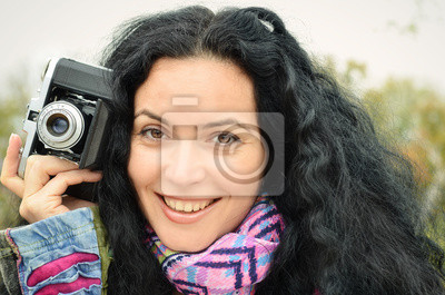 Young brunette girl with old photo camera taking picure