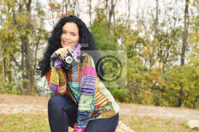 Young brunette lady with old photo camera on film
