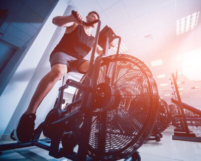 Sticker Young men with muscular body using air bike for cardio workout at cross training gym.