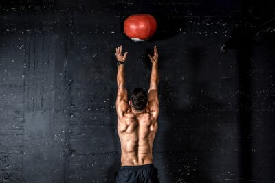Sticker Young strong sweaty focused fit muscular man with big muscles doing throwing medicine ball up on the wall for training hard core workout in the gym real people selective focus
